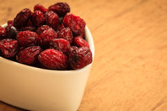 Dried cranberry fruit in bowl on table. Stock Photo