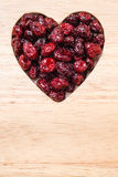 Dried cranberry fruit heart shaped on wood board Royalty Free Stock Image