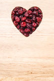 Dried cranberry fruit heart shaped on wood board Stock Photo