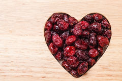 Dried cranberry fruit heart shaped on wood board Stock Images