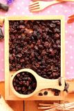 Dried currants on a wooden tray. Stock Image