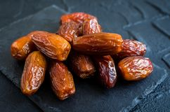 Dried dates on black stone background Royalty Free Stock Photography