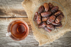 Dried date fruit with hot tea. Dried date fruit on glass plate over wooden table. with glass of tea. Fade and Warm color tone with dark vignette. Favorite and Royalty Free Stock Photo
