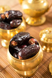 Dried date fruits in golden metal bowl. Royalty Free Stock Photos