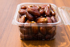 Dried date fruits in plastic container on wooden table Royalty Free Stock Photos