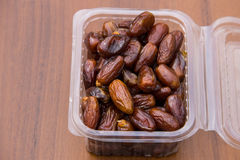 Dried date fruits in plastic container on wooden table Royalty Free Stock Image