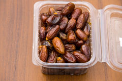 Dried date fruits in plastic container on wooden table Royalty Free Stock Photography
