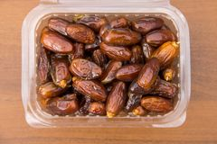Dried date fruits in plastic container on wooden table. Top view Royalty Free Stock Images