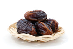 Dried dates. In a wicker bowl on the isolated background Royalty Free Stock Photos