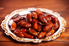 Dried dates. Beautiful background with dried dates on a silver tray on wooden background.  The Muslim feast of the holy month of Ramadan Kareem Stock Photography