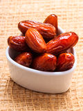 Dried dates in bowl on table background Stock Image