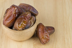 Dried dates in the bowl on the wood table Stock Photos