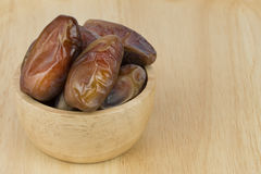 Dried dates in the bowl on the wood table Stock Images