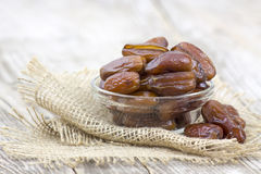 Dried dates in a bowl. On wooden background Royalty Free Stock Images