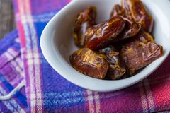 Dried dates in bowl on wooden table Stock Photos