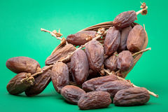 Dried dates. With a green background . according to the theme of the Muslim month of fasting , Glucose and sweetness Stock Photo