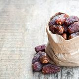 Dried  dates in paper bag  on wooden table. Dried  dates in paper bag on wooden table Royalty Free Stock Image
