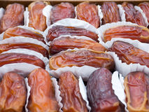 Dried dates in the paper wrappings. Arranged closely to each other Stock Photos