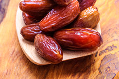 Dried dates on spoon wooden background Royalty Free Stock Photography