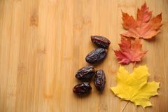 Dried dates on a wooden bamboo background in autumn style royalty free stock images