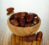 Dried dates. In a wooden bowl on a brown table close-up Stock Image