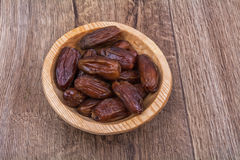 Dried dates in a wooden bowl on a wooden background. Dried dates in a wooden bowl on a brown wooden background Stock Image