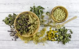Dried different herbs on wooden background. Dry different herbs in bowls on wooden background - herbs mix royalty free stock images