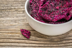 Dried dragon fruit (pitaya). Slices of dried red dragon fruit in a white, ceramic bowl against grained wood Stock Photos