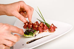 Dried duck breast with working human hands Stock Image