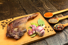 Dried duck meat. Dried duck thigh on the board with spices in spoons and black pepper with garlic Royalty Free Stock Photography