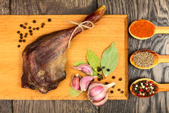 Dried duck meat. Dried duck thigh on the board with spices in spoons and black pepper with garlic Stock Photos