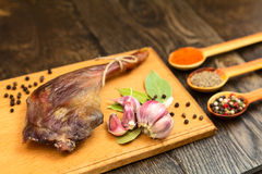 Dried duck thigh on the board. With spices in spoons and black pepper with garlic Stock Photo