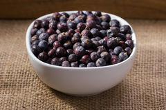 Dried elderberries in small white bowl. On linen, cloth background Stock Photo