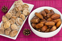 Dried figs and dates. On a pink background Royalty Free Stock Images