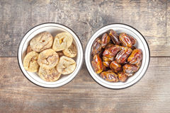 Dried figs and dates in bowls on wooden background Royalty Free Stock Photos