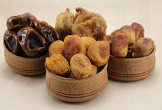 Dried figs, dates, dried apricots in a wooden circular shape. Against a background of natural fabrics Stock Photos