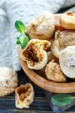 Dried figs and mint in a wooden bowl. Stock Photo
