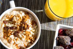 Dried figs, oatmeal and orange juice breakfast setting Stock Photography