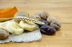 Dried figs, palms, pumpkins, wheat with walnuts and kiwis. Dried figs, palms, pumpkins with walnuts and kiwis on a wooden table royalty free stock photography