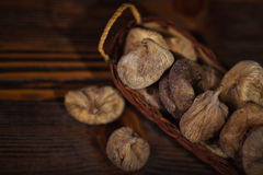 Dried figs in a small basket on wooden background Stock Photos