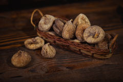 Dried figs in a small basket on wooden background Royalty Free Stock Photography