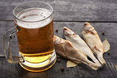 Dried fish and beer glass on a wooden table in a pub Royalty Free Stock Image