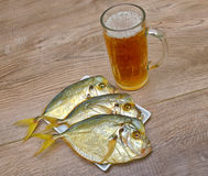 Dried fish and a glass of beer on a wooden table. Royalty Free Stock Image