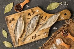 Dried fish with salt and pepper on cutting board Stock Images