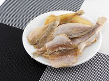 Dried fishes on white plate Stock Photography