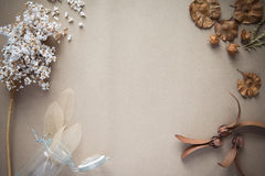 Dried flowers on brown paper background. Desk work in the spring, the vintage, the background color is brown Kraft paper Royalty Free Stock Photo