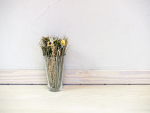 Dried flowers and grasses in glass vase against concrete wall.  Stock Photo