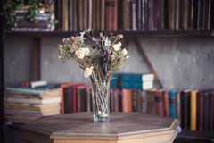Dried flowers in a vase on the library table royalty free stock photos