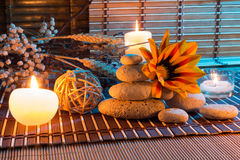Dried flowers, white stones, candles on bamboo mat. For massage royalty free stock photography