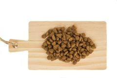 Dried food for dogs or cats on wooden cutting board. Pet care.  royalty free stock photos